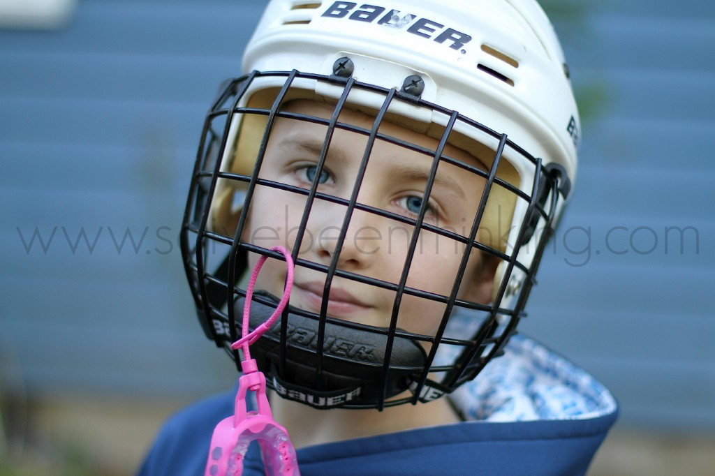 blue eyed boy in Bauer hockey helmet with pink mouthguard