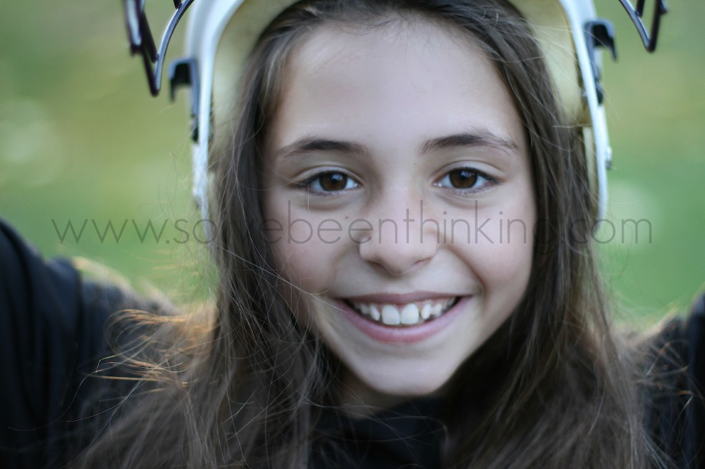 Brown Eyed Girl pulling off a hockey helmet smiling at the camera